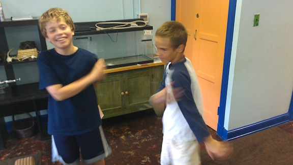 Sixth graders developing non-locomotor movements to represent the nucleus of an electrically charged atom.